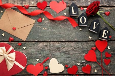 Hearts with red rose, gift box and envelope on wooden table