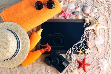 Seashells with wooden frame and beach accessories
