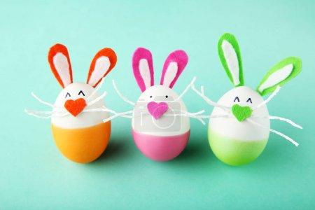 Photo pour Œufs avec des visages de lapin drôles sur fond de menthe - image libre de droit