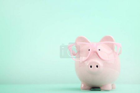Pink piggy bank with glasses on mint background