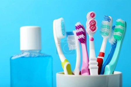 Photo pour Gros plan de brosses à dents colorées dans une tasse avec une bouteille de bain de bouche sur fond bleu - image libre de droit
