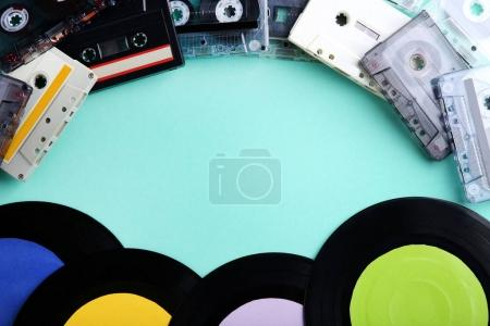Vinyl records and cassette tapes on mint background