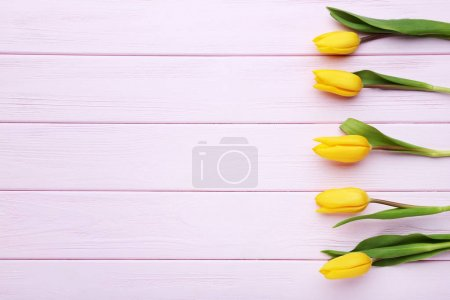 Bouquet of yellow tulips on pink wooden table