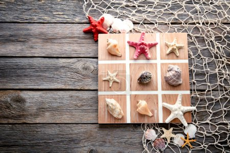 Tic tac toe game by seashells and starfish on grey wooden table