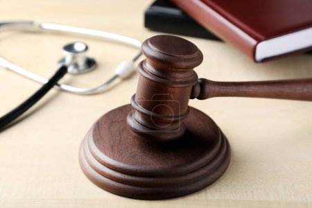 Judge gavel with stethoscope and book on wooden table
