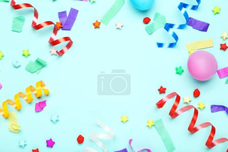 Colorful ribbons with rubber balloons and paper stars on blue ba