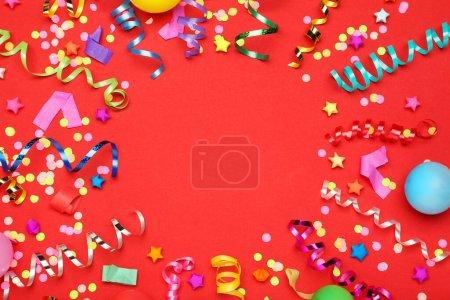 Photo pour Rubans colorés avec étoiles de papier et confettis sur fond rouge - image libre de droit