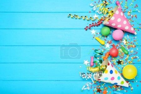 Photo pour Rubans colorés avec ballons, capuchons en papier et saupoudres sur fond de bois bleu - image libre de droit