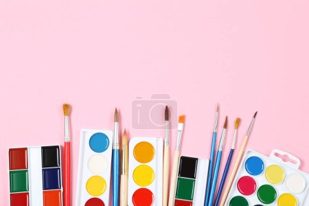 Photo for Colorful gouache paints and brushes on pink background - Royalty Free Image