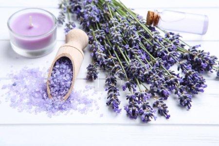 Photo pour Fleurs de lavande avec l'huile dans la bouteille, la bougie et le sel sur la table en bois blanche - image libre de droit