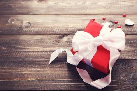 Photo pour Boîte-cadeau avec ruban et cœurs sur table en bois - image libre de droit