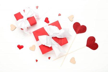 Photo pour Boîtes-cadeaux avec rubans et cœurs sur table blanche en bois - image libre de droit