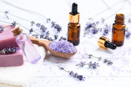 Photo pour Fleurs de lavande avec huile en bouteille, savon et sel sur table blanche en bois - image libre de droit