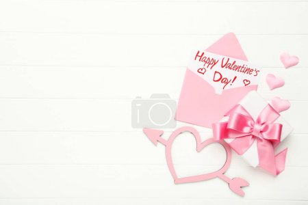 Photo for Paper envelope with hearts, gift box and text Happy Valentines Day on white wooden table - Royalty Free Image