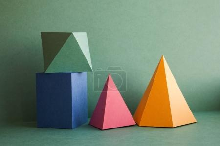 Abstract geometrical solid figures still life. Colorful three-dimensional pyramid prism rectangular cube arranged on green background. Yellow blue pink malachite colored objects textured paper surface