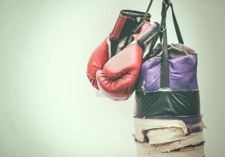Photo for Photograph of an old punching bag and a pair of boxing gloves - Royalty Free Image