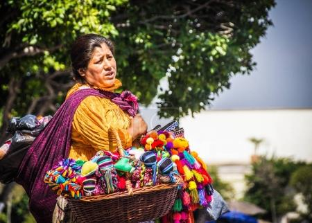 Mexican indigenous woman with traditional dress selling dolls