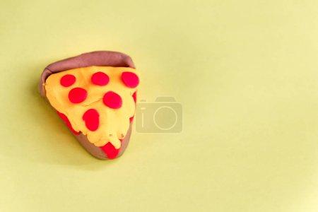 plasticine slice of pizza on yellow background