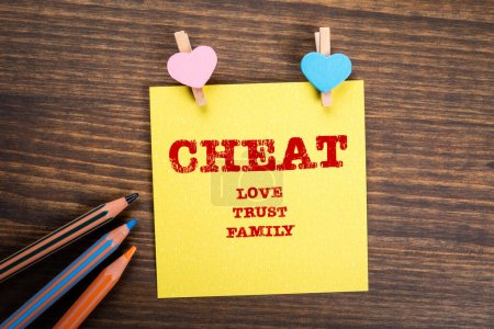 Photo for CHEAT. Love, trust and family concept. Wooden clips with heart and note on wooden table - Royalty Free Image