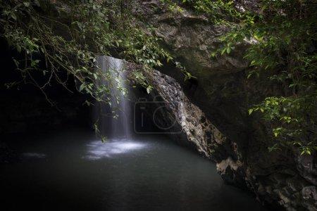 Photo pour Scène paisible de cascade dans une grotte sombre - image libre de droit