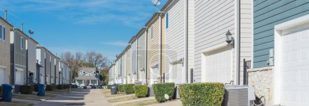 Photo for Panorama back alley of new development residential community, line of two-car garage door in Coppell, Texas. Colorful two story houses row well trim landscape near downtown Dallas, outdoor AC units - Royalty Free Image
