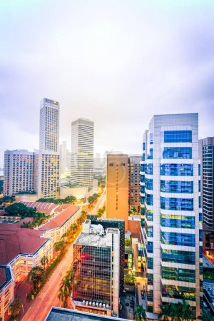 Photo for Aerial view office and residential buildings in downtown Singapore with skylines in background. Illuminated lights from skyscrapers and traffic on the main street. - Royalty Free Image