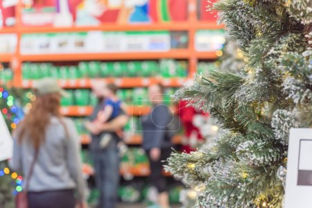 Photo for Shallow DOF on white artificial Christmas tree with defocused customer shopping in background. Microdot and multi-lights pre-lit Xmas decoration display at home improvement store in USA - Royalty Free Image