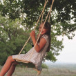 Mother plays with her daughter on swing on an oak ...