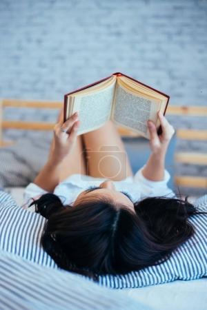 Photo pour Femme lisant le livre sur son lit le matin à la maison - image libre de droit