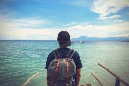 Foto de La parte posterior del backpacker hombre parado en el borde de la playa de la costa disfrutando de tiempo libre - Imagen libre de derechos