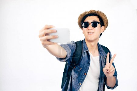 Photo for Young Asian tourist with hat smiling and holding smartphone taking a selfie photo isolated over white background - Royalty Free Image
