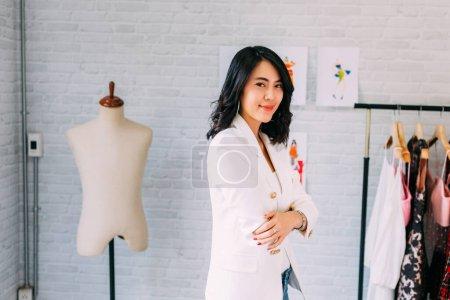Photo pour Contenu Créateur de mode asiatique debout à table et ayant les bras croisés avec de l'équipement de couture et souriant à la caméra dans un atelier de lumière - image libre de droit