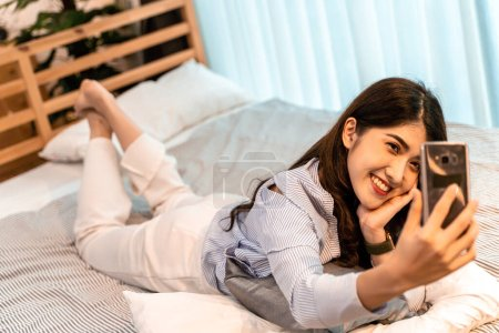Photo for Happy young woman taking selfie photo with her mobile phone while lying down in bedroom at home. Beautiful Asian girl making a video call inside her house. - Royalty Free Image