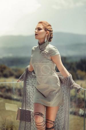 woman wearing dress standing on balcony