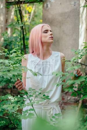 Photo pour Jeune femme avec les cheveux roses et sensuel dans le jardin de conte de fées en été - image libre de droit