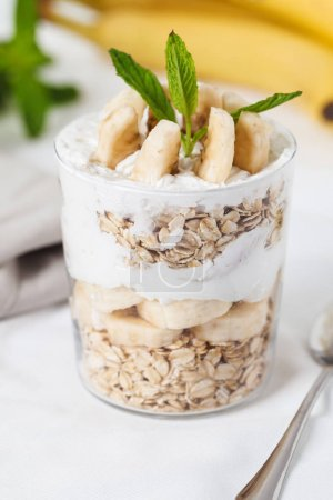 Banana breakfast with oat in a jar on white background