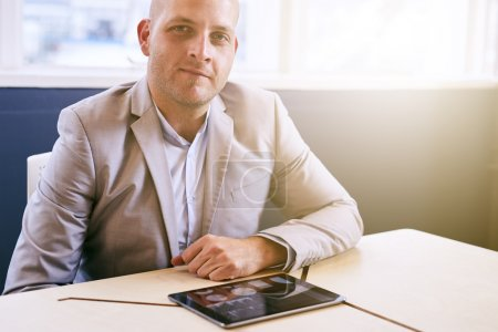 Man looking at camera with tablet in front of him