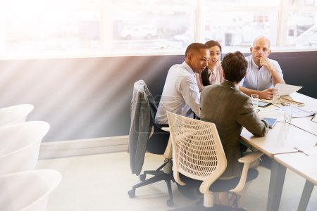 Four eclectic business individuals conducting a meeting in conference room