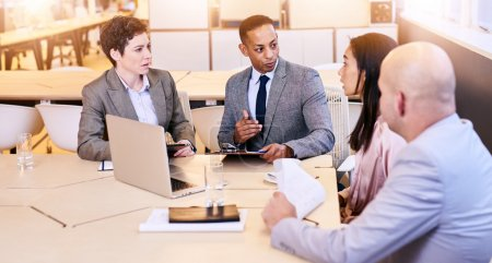 Eclectic group of four business professionals conducting a meeting