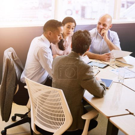 Four business professionals in a meeting indoors
