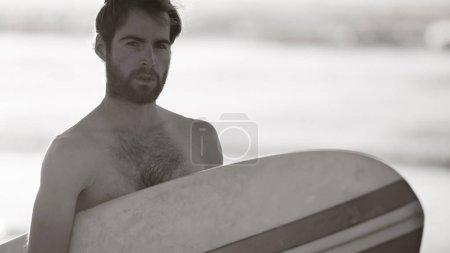 Photo pour Image noir et blanc du jeune internaute masculin tenant une planche de surf sous le bras tout en regardant la caméra avec la pause de vagues d'océan dans le fond derrière lui. - image libre de droit
