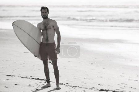 Photo pour Image noir et blanc de la jeune surfeuse mâle debout sur la plage avec sa planche de surf sous le bras et les vagues de l'océan derrière lui en arrière-plan. - image libre de droit