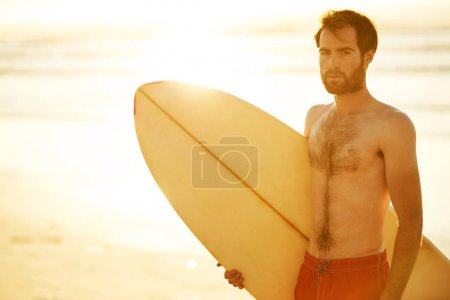 Handsome surfer holding a surfboard under his arm on beach