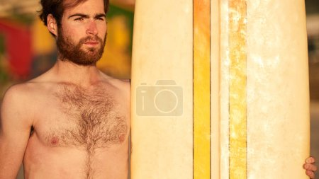 Photo pour Gros plan horizontal image de barbu surfeur caucasien debout à côté de sa planche de surf avec un fond coloré. - image libre de droit