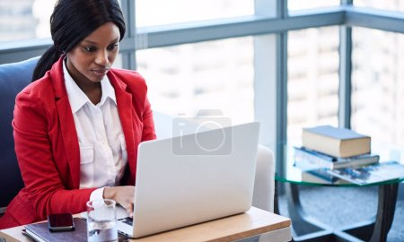 black businesswoman busy working while looking at her computer screen