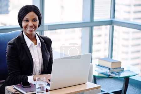 Black businesswoman busy smiling at the camera seated behind computer
