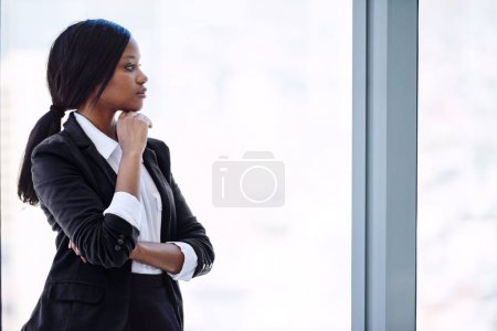 African business woman looking out window in thought about investments