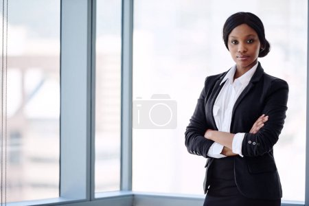 Formally dressed blackbusiness woman looking at camera with arms crossed