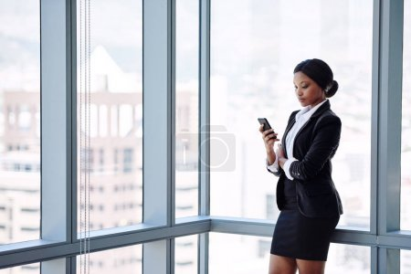 Mature black business woman texting while standing