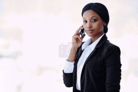 Photo for Young attractive, well dressed black businesswoman looking at camera with a serious facial expression while holding her phone against her ear in her right hand - Royalty Free Image